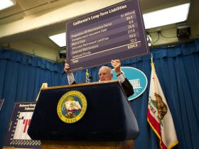 Calif. Gov. Jerry Brown holds up a chart of the state's long-term debts as he presents his budget proposal in January 2014.