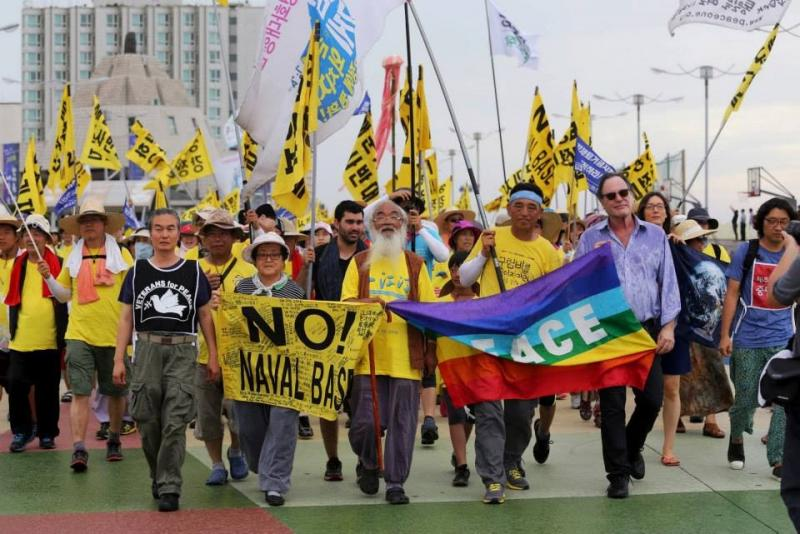 Protesters march in opposition to the Jeju Island naval base. Among them are Nicholas Sismil (in black short), noted Korean activist Father Mun, and, at the far right, American filmmaker Oliver Stone.