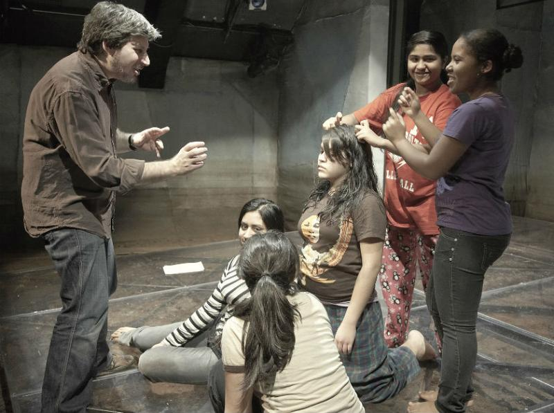 "Albany Park Theater Project Director Davie Feiner works with the young cast of ""Remember Me LIke This"""