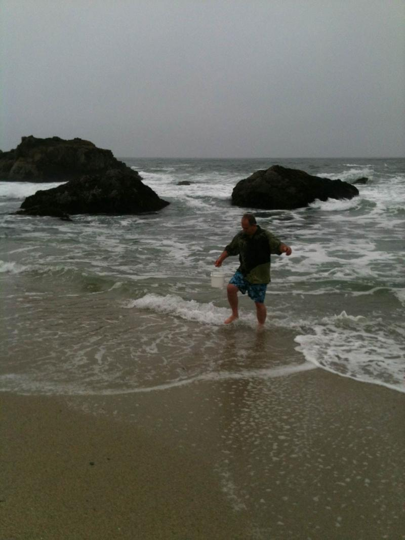 Dan Sythe,  volunteer and founder of International Medcom Inc., returns from the ocean with a bucket of sea water.