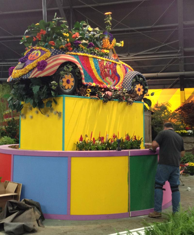 "A ""flower-powered"" Volkswagen atop a arotating turntable gets some finishing touches on Monday."