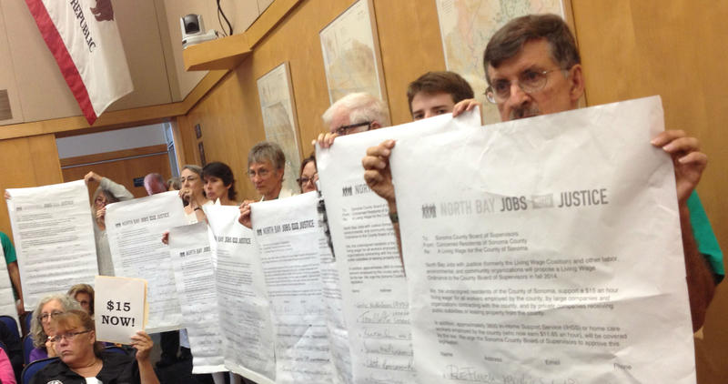 Living Wage advocates (including Marty Bennett, far right) unfurled enlarged copies of petitions calling for a new $15 per hour rate as the 2200 regular size petitions were presented to County Supervisors Tuesday afternoon.