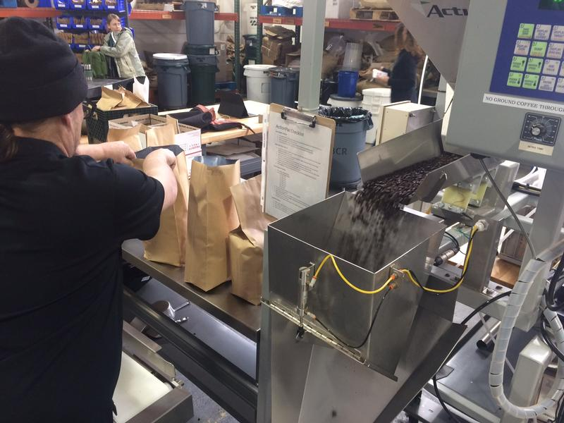 Timothy Kitchen moves five pound bags of roasted coffee beans down the conveyor.