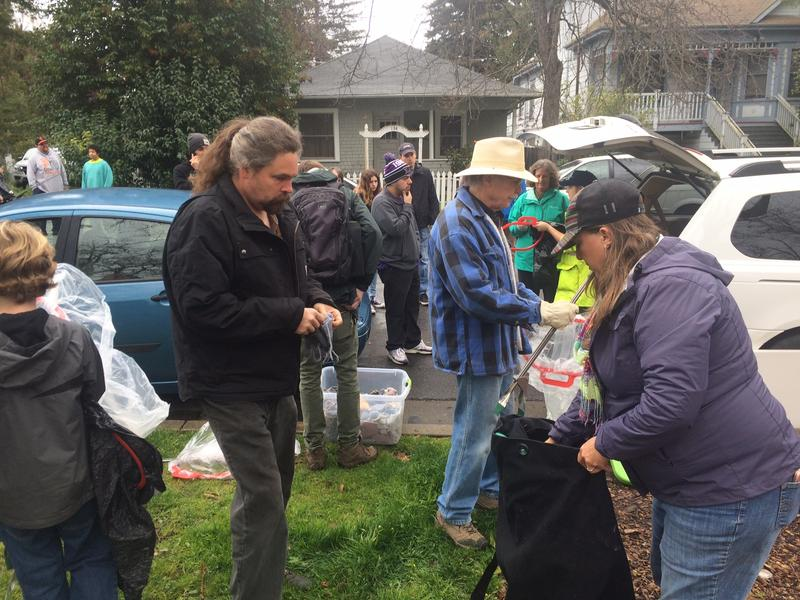 Creek cleanup organizer Stephanie Lennox hands out trash bags and pickers to volunteers.
