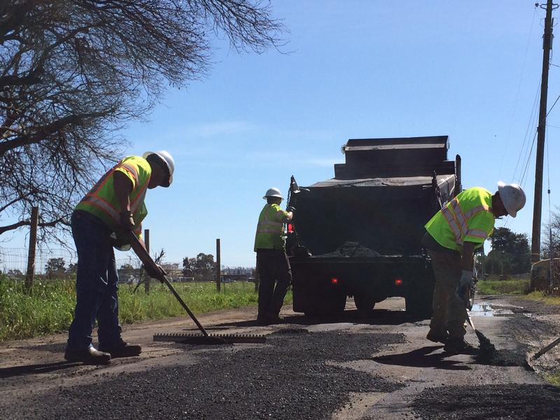 Hot asphalt is shoveled by hand onto potholes before being compacted by a roller.