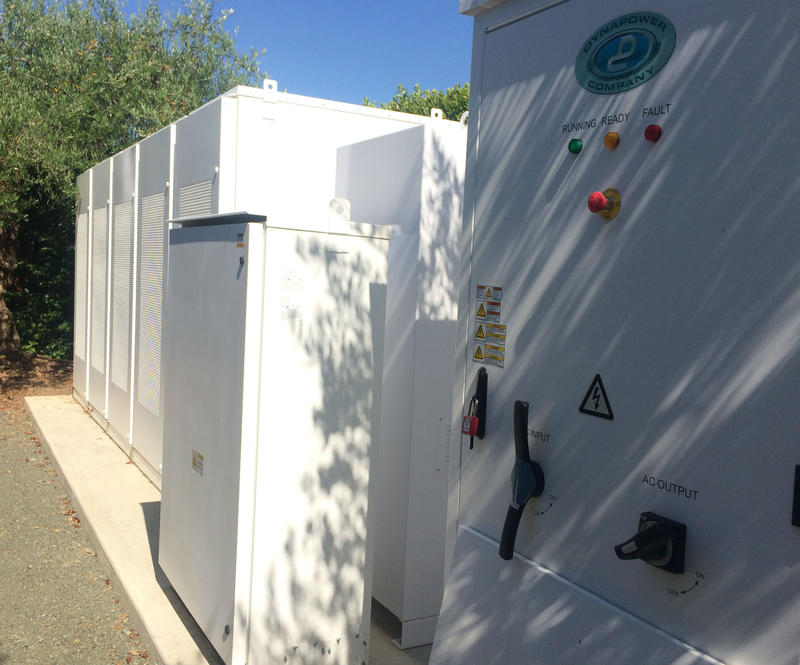 Massive banks of batteries, screened by landscaping and linked by underground conduits, hold and dispense the large quantities of reenewable energy generated at multiple sites around the farm's grounds.