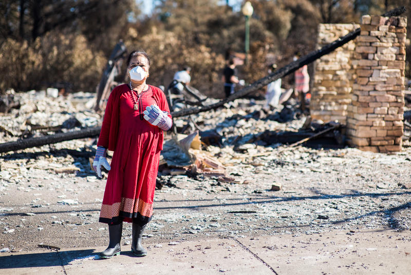 Woman in red amid Fountaingrove fire damage