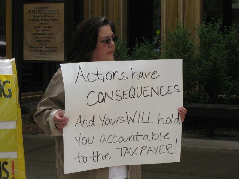 A critic of Sheriff Terry Maketa holds a sign outside the El Paso County Sheriff's Department