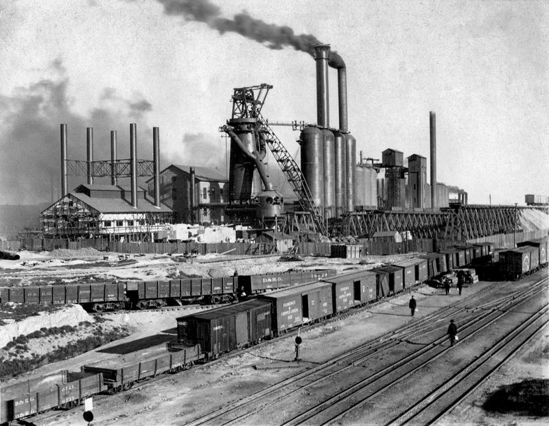 General view of the CF&I blast furnace row and rail yard before the steel mill was fenced. Denver and Rio Grande rail cars are in the foreground. Date is unknown but most likely in the 1910-1920s.