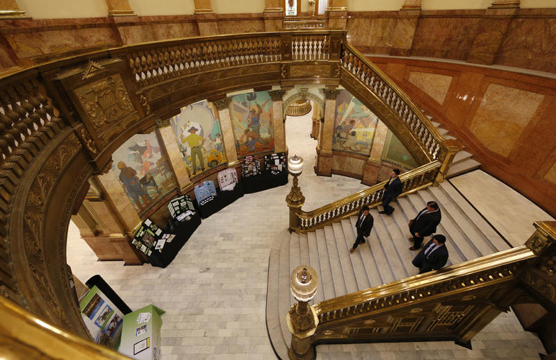 A group of men head down the central staircase in the Colorado State Capitol, Tuesday, April 5, 2016, as lawmakers meet in session. The Colorado Legislature will meet for roughly another month before closing the 2016 session.