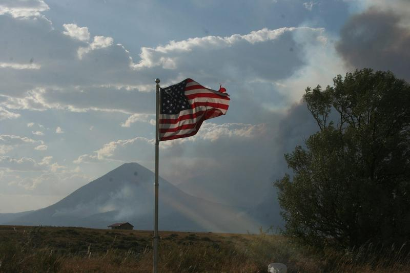 Smoke from the Spring Fire surrounds an American Flag.