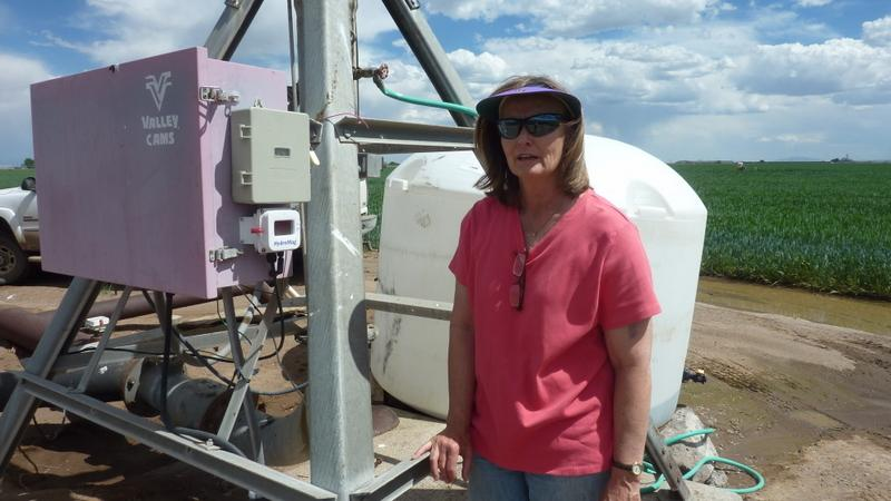 Karla Shriver stands by a pumping system that draws water from the aquifer.