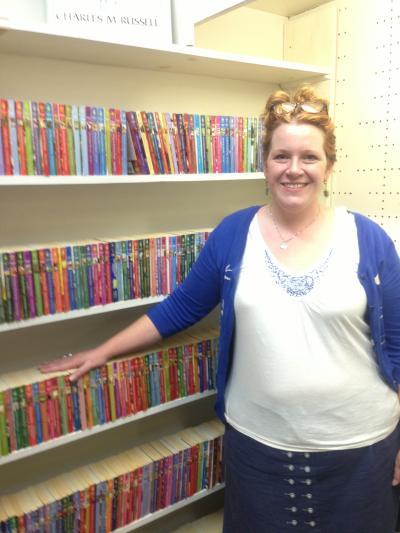 Rachel Reynolds Luster stands in front of the Myrtle public library's paperback romance novels; she estimates one third of the library's entire collection is currently dedicated to that genre, something she hopes to change.