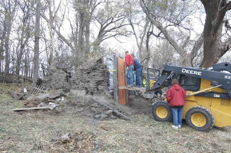 Researchers prepare to take down a section of a sod house in Gates, Neb., in order to study the bricks made of dirt.