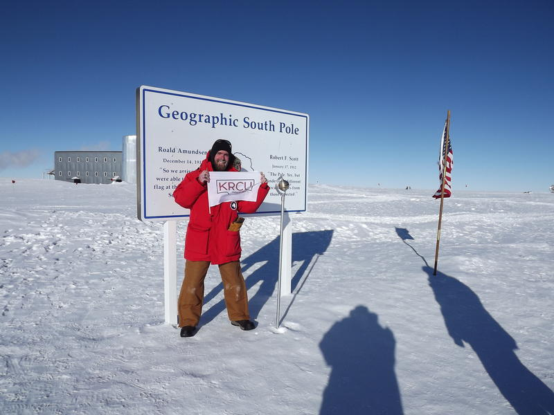 William Lindman holding a KRCU flag in Antarctica.