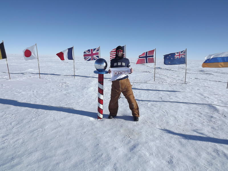 William Lindman holding a KRCU flag in Antarctica.