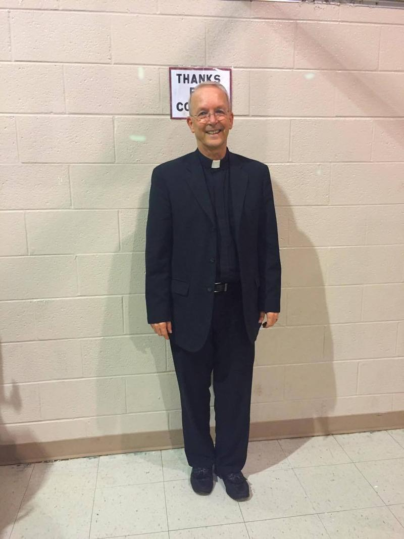 Father Michael Casteel waits for his takeout food at the smorgasbord dinner.