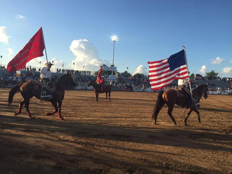 Cowboys ride around the arena carrying flags.