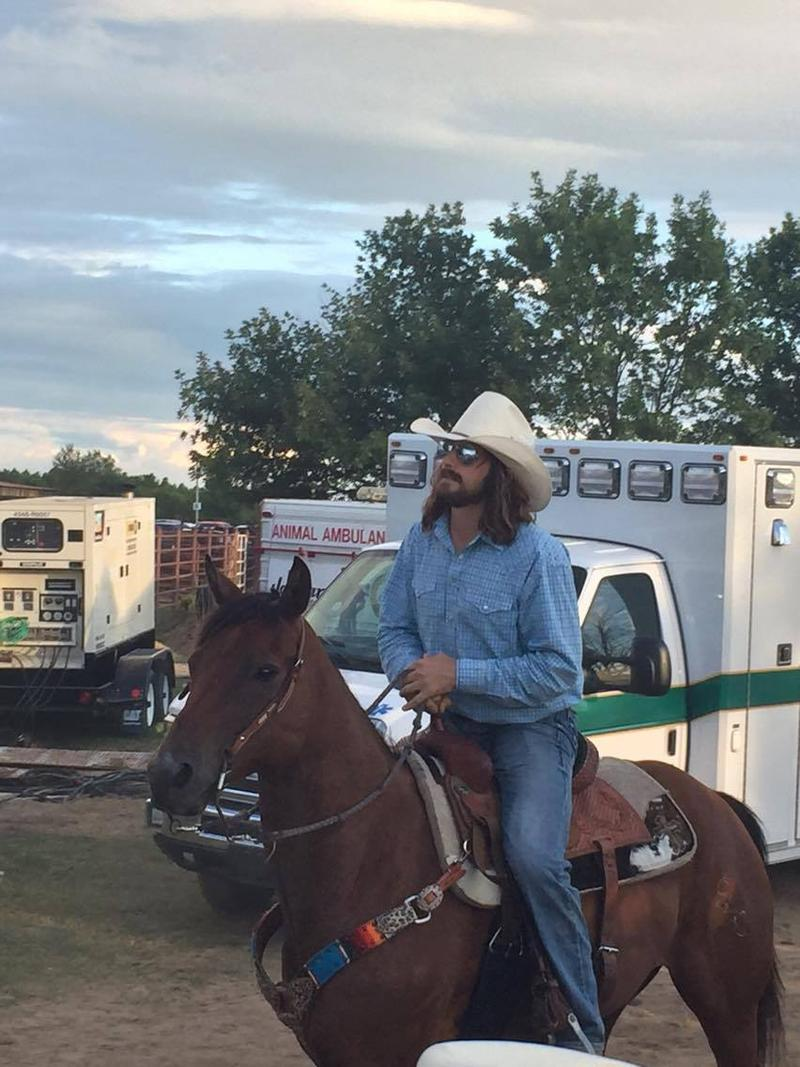 Cowboy and social media star Dale Brisby rides his horse into the arena at the Jaycee Bootheel Rodeo.