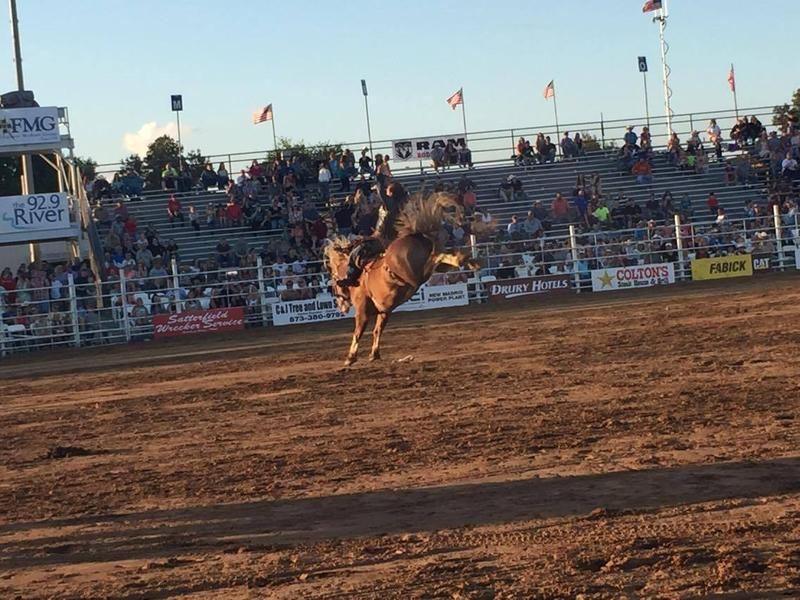 A cowboy rides a bucking horse at the Jaycee Bootheel Rodeo.