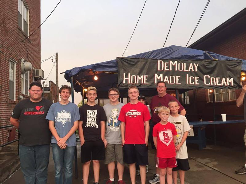 Rodney Pensel, far back right, and his team of young workers serve Demolay ice cream at Jackson Homecomers.