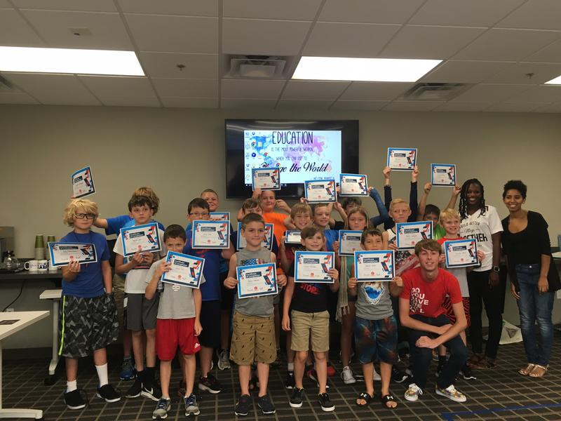 Participants of the Kid's Coding Camp hold up their Certificates of Completion after presenting their Finch routines to judges.