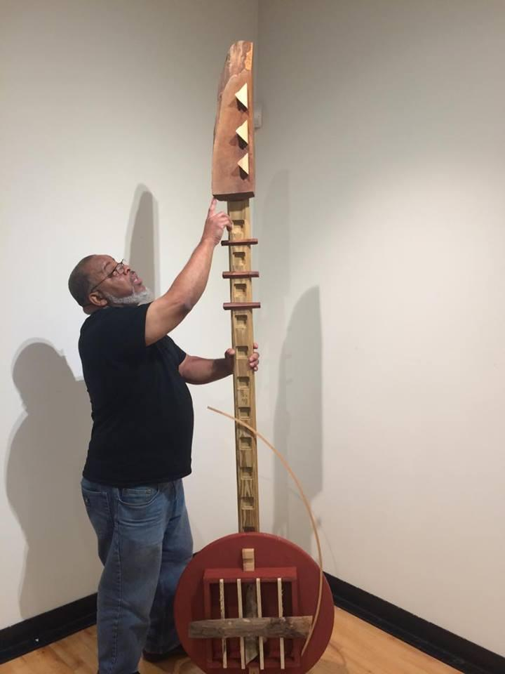 Najjar Abdul-Musawwir, an associate professor of fine arts at Southern Illinois University points to a banjo piece for his new exhibition.