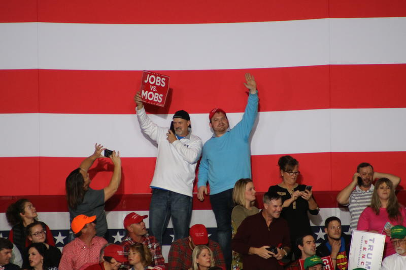 Supporters stand in front of an American flag at last night's rally.