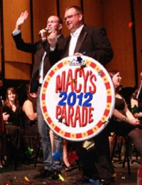 Professor Brian Taylor holds a sign in support of the Band's appearance at the Macy's Thanksgiving Day parade