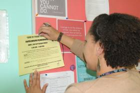 Operations Manager of Faith House of Acadiana, Jessica Frazier, pins a flyer on the news board in support of one of the many fundraisers Faith House of Acadiana hosts.