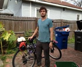 Will Adams stands beside his bike in the yard of the house he stayed in while in Lafayette.