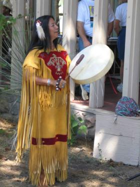 Yolanda Martinez in Native American dress with drum.