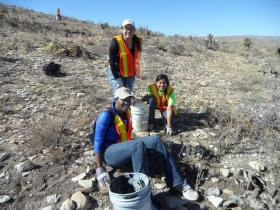 Volunteers help to remove weathered glass and assorted metal objects from an old dumping site at Carlsbad Caverns National Park./NPS Photos