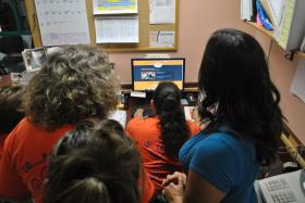Animal Services Center of the Mesilla Valley director Dr. Beth Vesco-Mock, left, gathers with shelter staff to view the official online posting of winners in the 2013 ASPCA Rachael Ray $100k Challenge. The shelter placed sixth in the national challenge, bringing $15,000 in prize money to Doña Ana County.