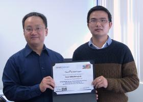 Joe Song, left, NMSU computer science professor, and student Yang Zhang show off their Best Performance certificate from the HPN-DREAM8 challenge. The team scored first place in one of three challenges in the competition. (Photo by Isabel Rodriguez)