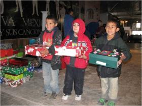 Palomas boys receive Christmas Shoe Boxes filled with gifts.