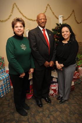 Tina Hancock, NMSU School of Social Work Director, Tilahun Adera, NMSU College of Health and Social Services Dean, and Gloria Nunez, NMSU School of Social Work event planner, stand in front of the angel tree the NMSU School of Social Work sponsors. Gifts are donated to children in foster care through the New Mexico Children Youth and Families Department. (NMSU photo by Darren Phillips)