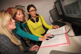 Linda Spencer, center, director of the Communication Disorders Program in New Mexico State University's College of Education, talks to her students Shelbie Claycomb, left, and Ruthie Montes who are working in her lab analyzing data for a research project. (NMSU Photo by Darren Phillips)