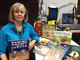 Dr. Anita Hernandez at KRWG FM studios with a few of the award-winning children's books.