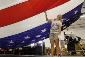 "New Mexico Museum of Space History curatorial volunteer, Hannah Earle, inspects this incredible 30'x50' American flag as the museum prepares to put it on display for the June 14th All-American Picnic and Sing-A-Long being held at the museum in conjunction with the Smithsonian's ""Raise it Up! Anthem for America"" celebration. Burt Broadcasting, Inc., is co-sponsoring the event which begins at noon on June 14th in the museum's upper parking lot."