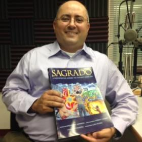 Dr. Spencer Herrera with his new book at the KRWG FM studios.
