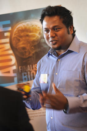 New Mexico State University engineering doctoral student Sasi Prabhakaran discusses a poster detailing adaptive singularity-free control moment gyroscope technology during a special event honoring six finalists in the Launch proof of concept program competition sponsored by NMSU's Arrowhead Center. Developed by NMSU engineering professor Amit Sanyal, the proposed ASCMG technology went on to win the competition. (NMSU photo by Darren Phillips)