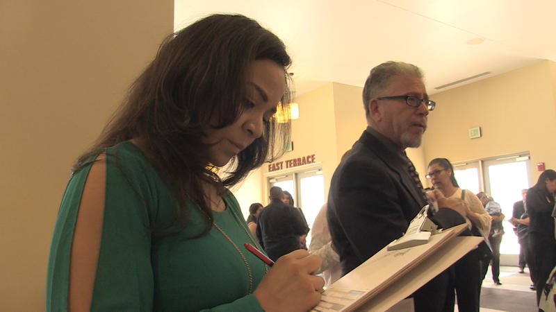 Recently naturalized resident Barbara Aguilera fills out a voter registration form.
