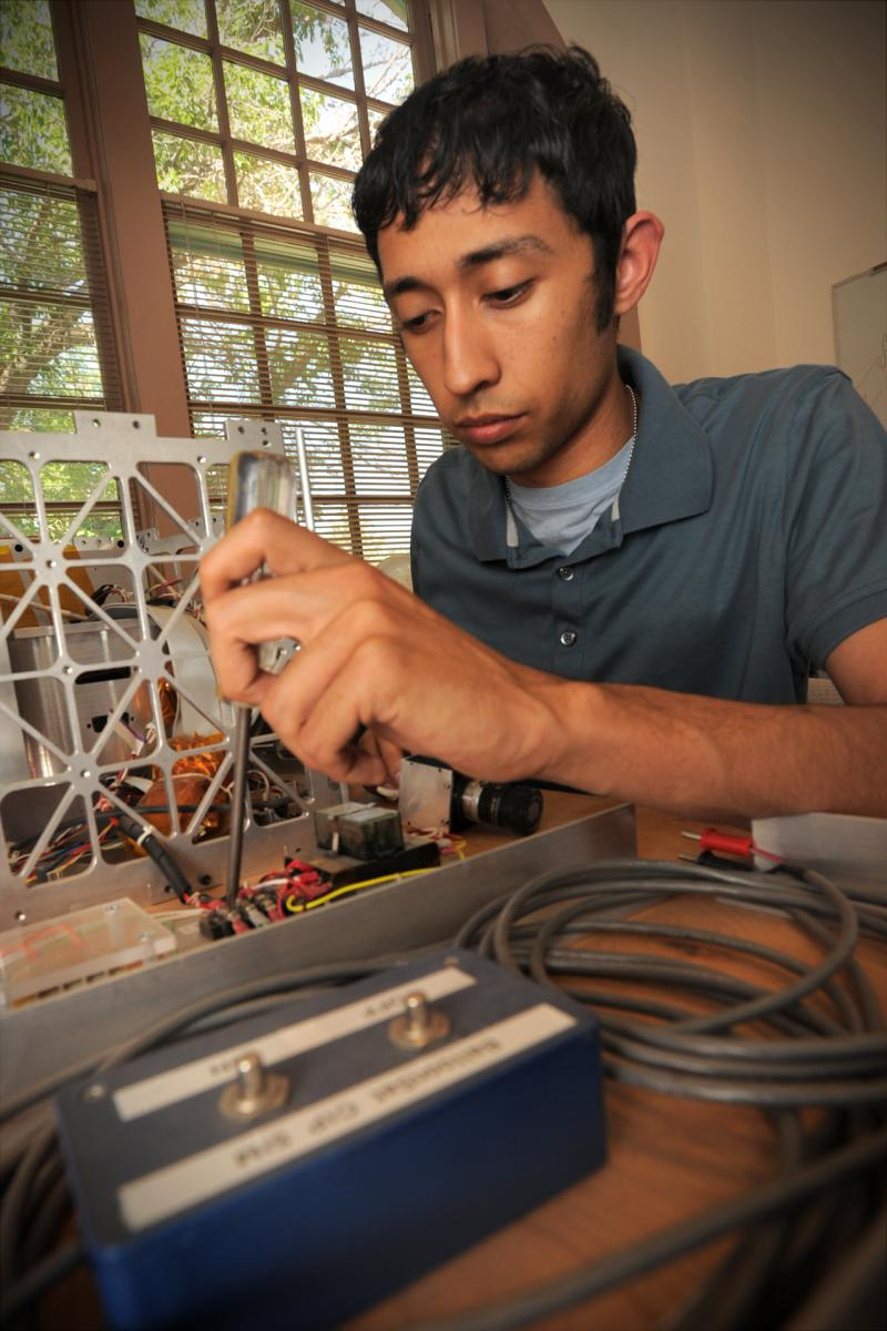 Engineering student Chris Galvan works on a nanosatellite inside one of the Goaddard Hall engineering laboratories. (photo by Darren Phillips)