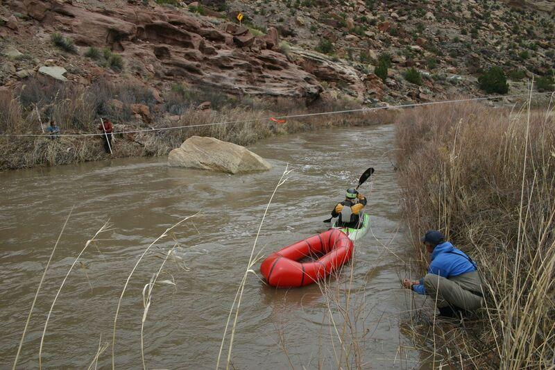 The Nature Conservancy's Celene Hawkins manuvers a raft strapped to monitoring equipment in the Lower Dolores River during a high-flow event in the spring of 2017