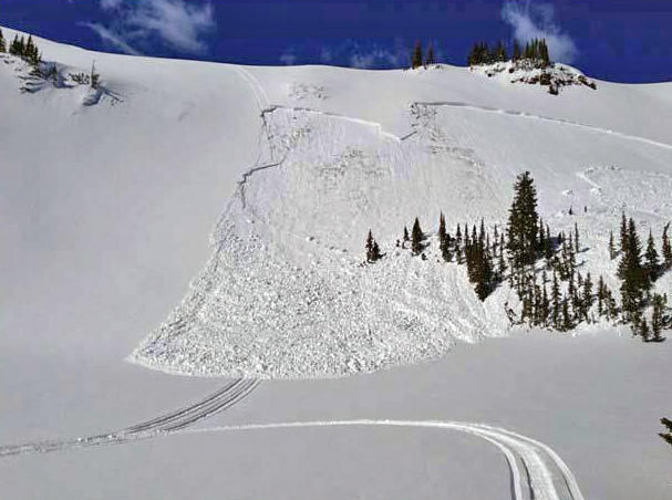 A slab avalanche is triggered by a snowmobile