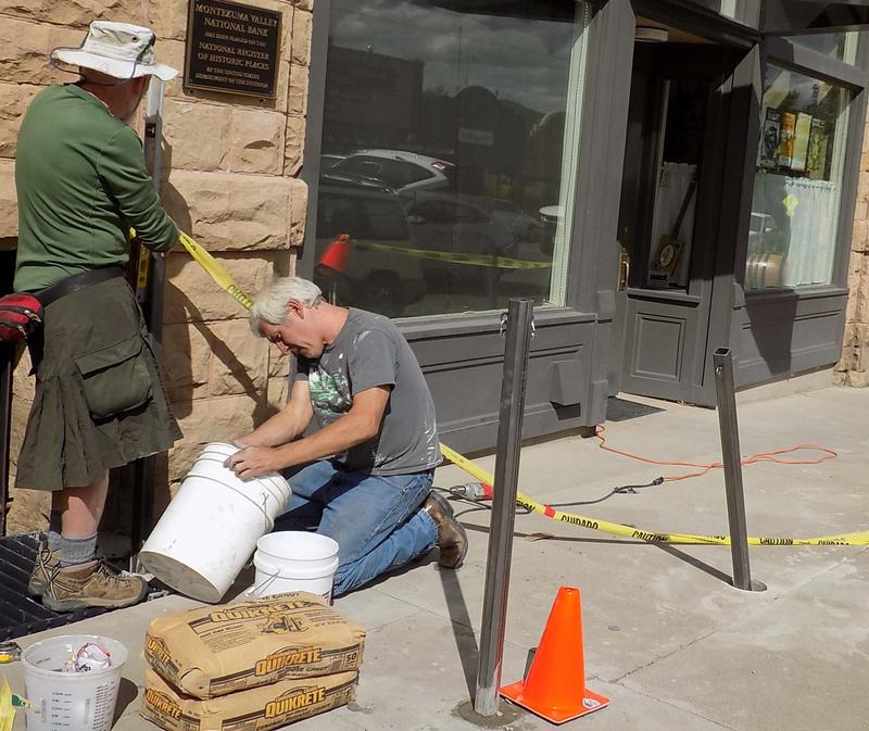 Jeff Pope (right), constructs a fence in front of the Sunflower Theatre in September 2016.