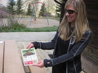 EcoAction Partners Executive Director Heather Knox shows off one of the fliers distributed as part of Ophir's new composting program.