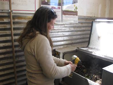 Ophir resident Jacey Depriest stirs the compost with a drill auger.