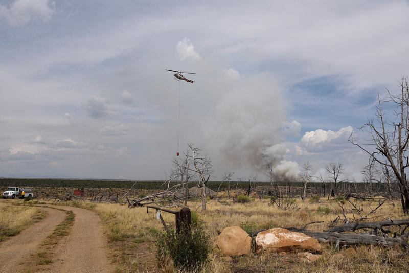 A support helicopter moves to refill its bucket for the Moccasin Mesa Fire on August 4.
